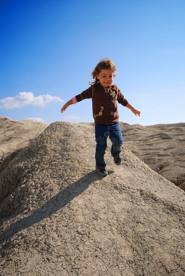 Kleines Mädchen, das hinunter Hügel läuft lizenzfreie stockfotos