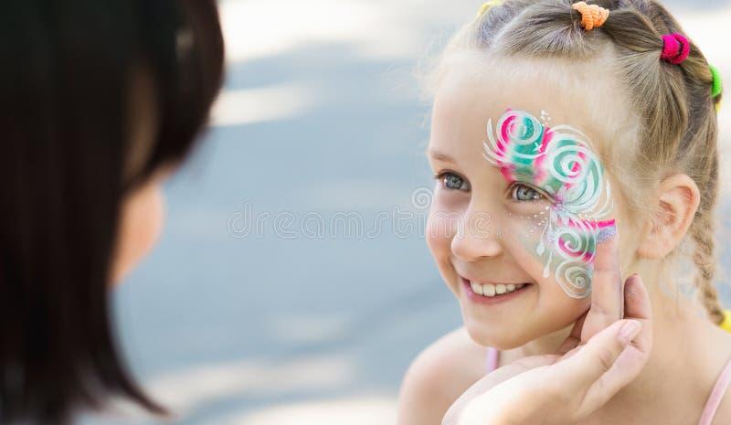 Kleines Mädchen, das ihr Gesicht gemalt vom Gesichtsmalereikünstler erhält lizenzfreie stockbilder