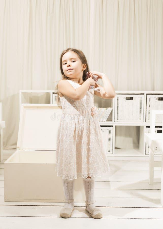 Kleines Mädchen, das ihr schönes langes Haar kämmt stockfotografie