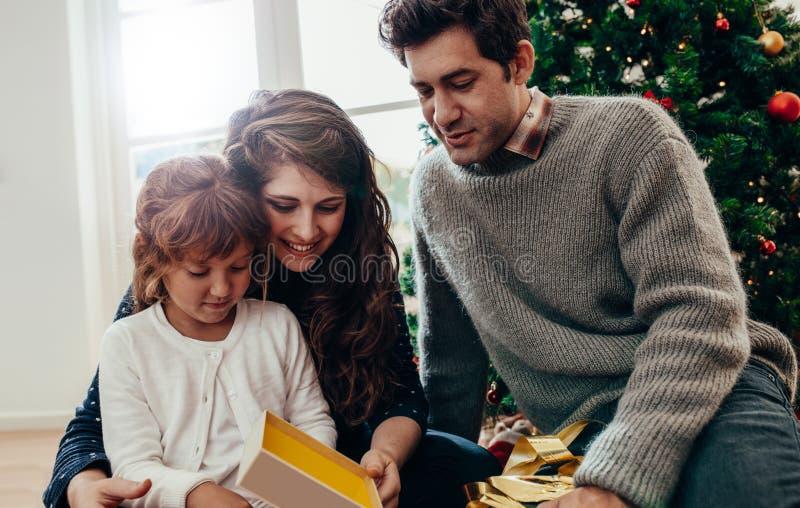 Kleines Mädchen, das ihr Weihnachtsgeschenk öffnet lizenzfreies stockfoto
