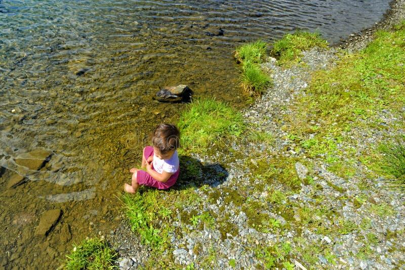 Kleines Mädchen, das ihre Füße in einem Gebirgsbach eintaucht stockfotos