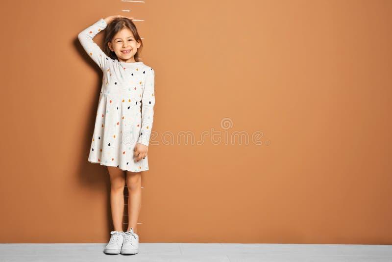 Kleines Mädchen, das ihre Höhe nahe Wand misst lizenzfreies stockbild