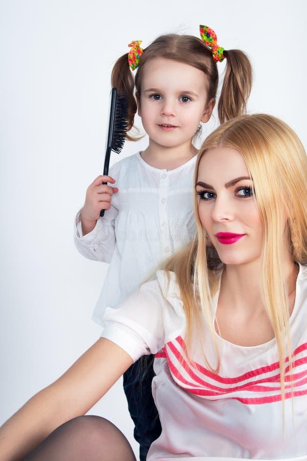 Kleines Mädchen, das ihre Haarmutter kämmt lizenzfreie stockbilder