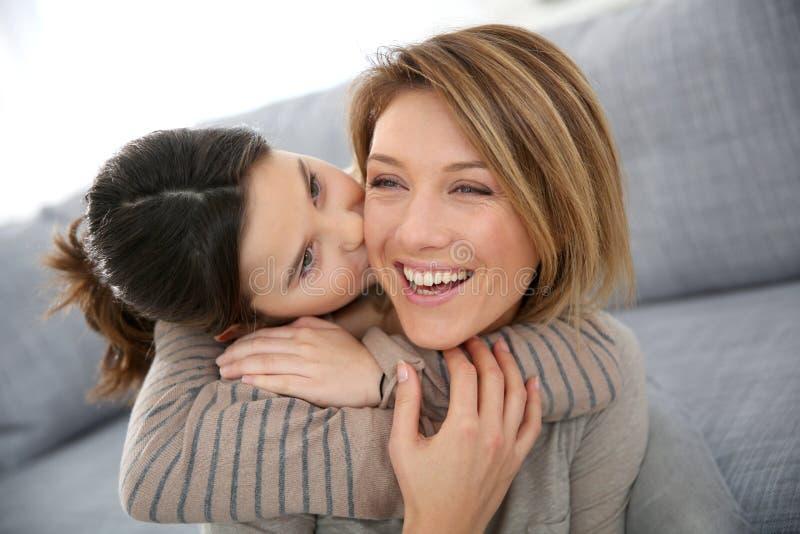 Kleines Mädchen, das ihre Mutter in der Backe küsst lizenzfreie stockfotos