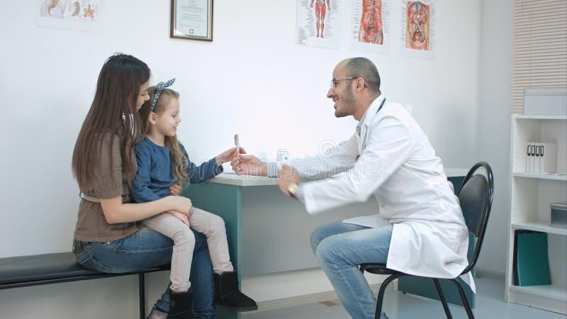 Kleines Mädchen, das ihre Mutter und lächelnden männlichen Doktor geben ihre Süßigkeit für gutes Verhalten küsst lizenzfreie stockfotografie