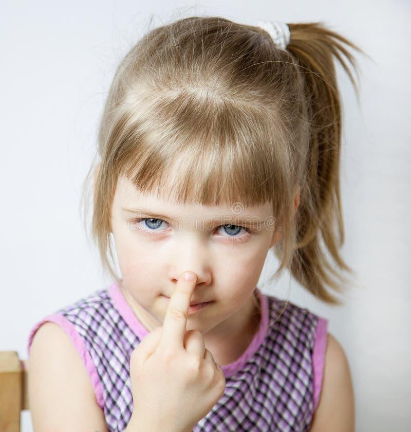Kleines Mädchen, das ihre Nase berührt stockfotos