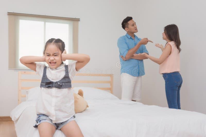 Kleines Mädchen, das ihre Ohren während streitenes Elternteil traurig und geschlossen worden sein würden stockfotografie