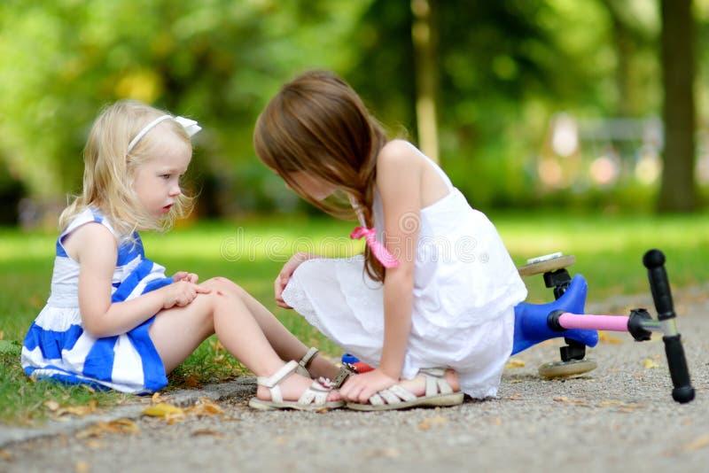 Kleines Mädchen, das ihre Schwester tröstet, nachdem sie beim Reiten ihres Rollers fiel stockfoto
