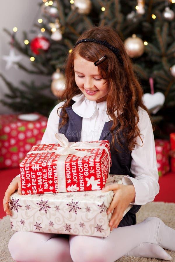 Kleines Mädchen, das ihre Weihnachtsgeschenke betrachtet lizenzfreies stockbild