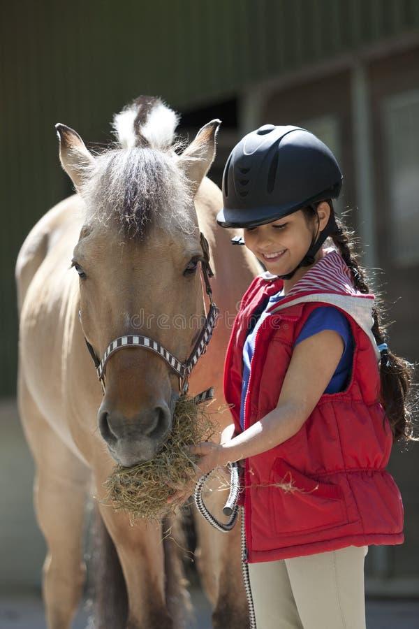 Kleines Mädchen, das ihrem Lieblingspferd etwas Heu speist stockbild