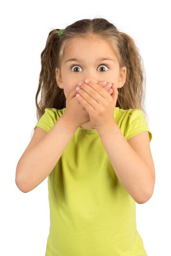 Kleines Mädchen, das ihren Mund bedeckt lizenzfreie stockfotos