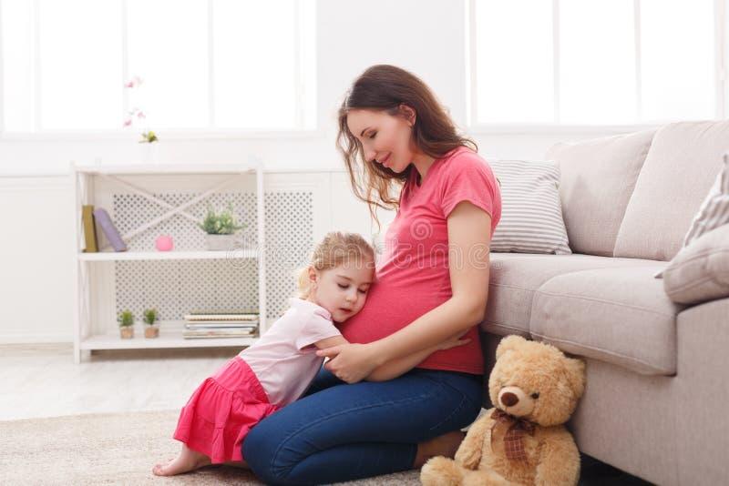 Kleines Mädchen, das ihren schwangeren Mutterbauch umarmt stockbilder
