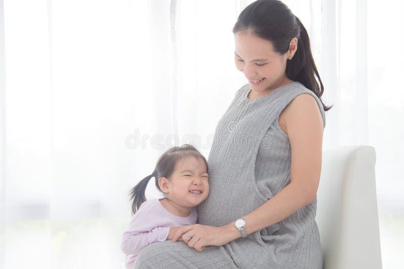 Kleines Mädchen, das ihren schwangeren Mutterbauch und -lächeln umarmt stockfoto