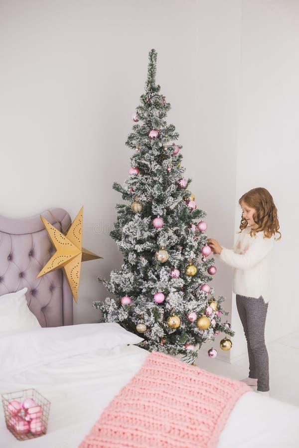 Kleines Mädchen, das ihrer Familie hilft, Weihnachtsbaum zu verzieren lizenzfreie stockfotografie