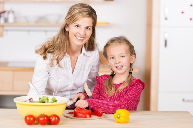 Kleines Mädchen, das ihrer Mutter mit dem Kochen hilft stockfoto