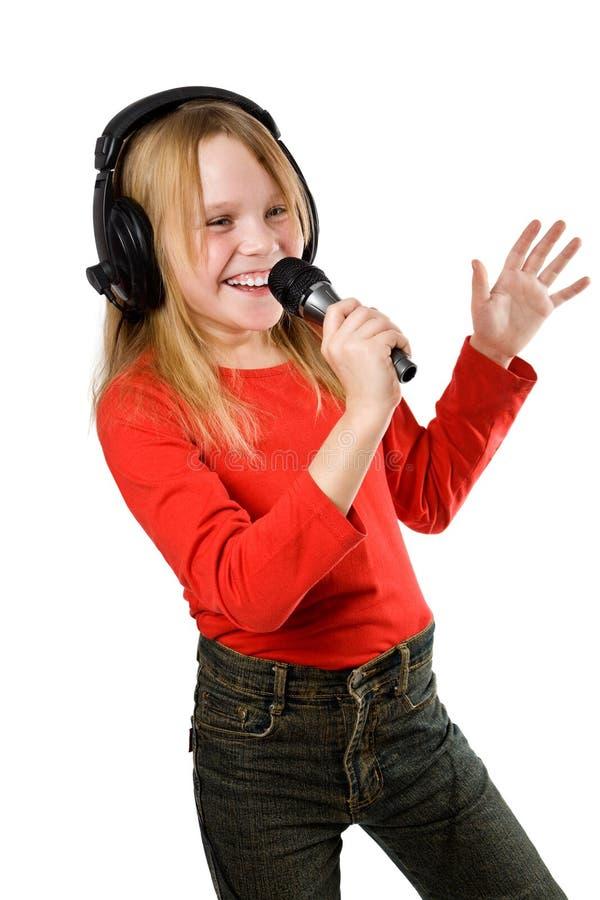 Kleines Mädchen, das im Mikrofon singt lizenzfreie stockfotografie