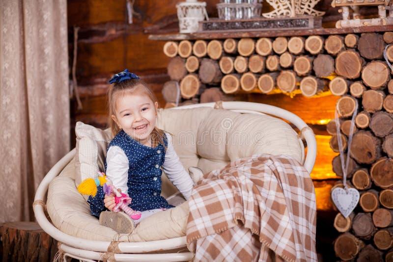 Kleines Mädchen, das im Schaukelstuhl nahe Kamin sitzt lizenzfreies stockfoto