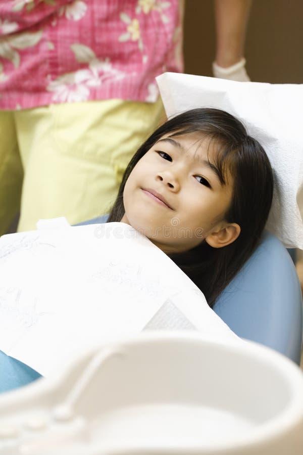 Kleines Mädchen, das im Stuhl des Zahnarztes sitzt stockfotos