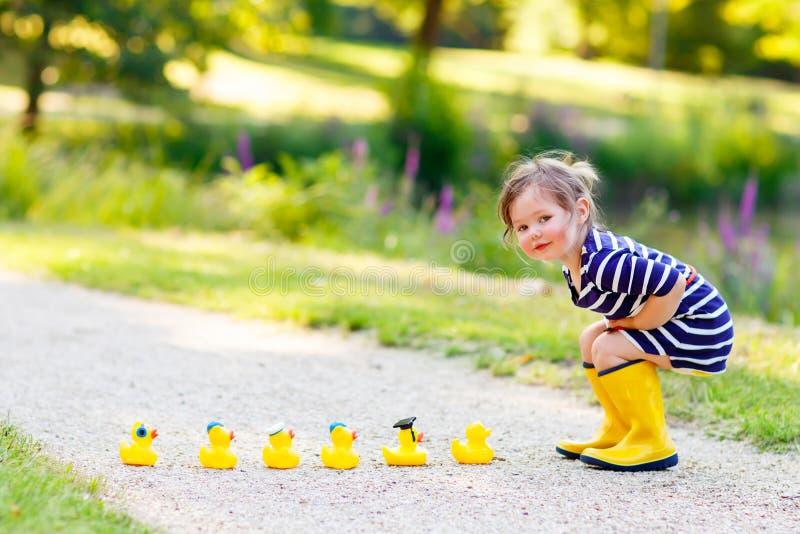 Kleines Mädchen, das im Wald und in tragenden Stiefeln spielt stockfoto