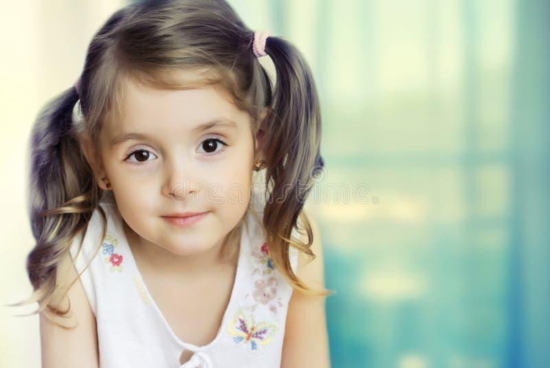 Kleines Mädchen, das Kamera betrachtet Kleine Kindernahaufnahme auf backgrou lizenzfreie stockfotos