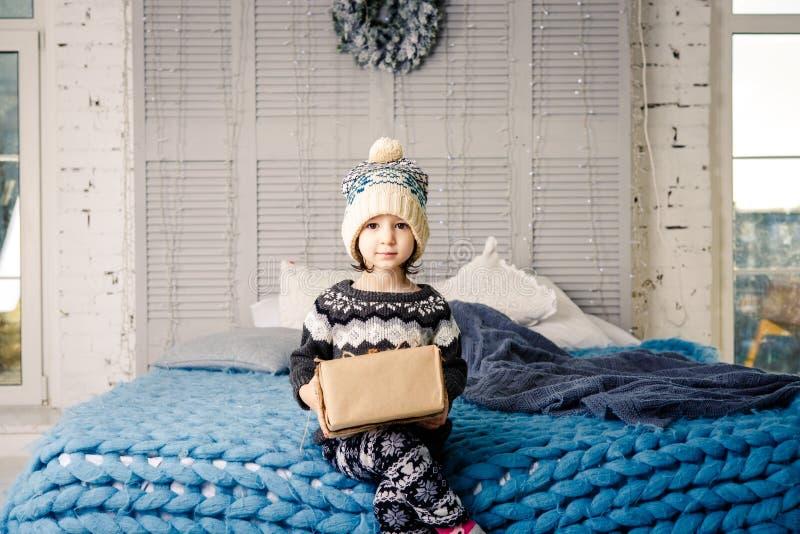 Kleines Mädchen das Kind, das in den Pyjamas und im Hut auf dem Bett mit Girlande von Glühlampen mit den Geschenkkästen eingewick stockfoto