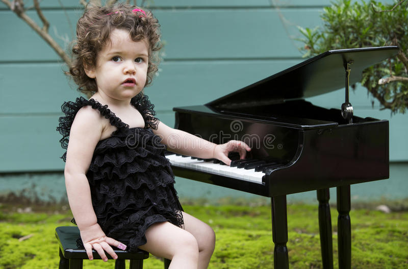 Kleines Mädchen, das Klavier spielt stockbild