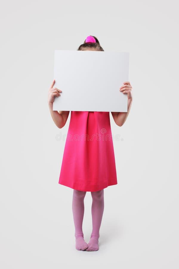 Kleines Mädchen, das leere Zeichen anhält lizenzfreies stockbild