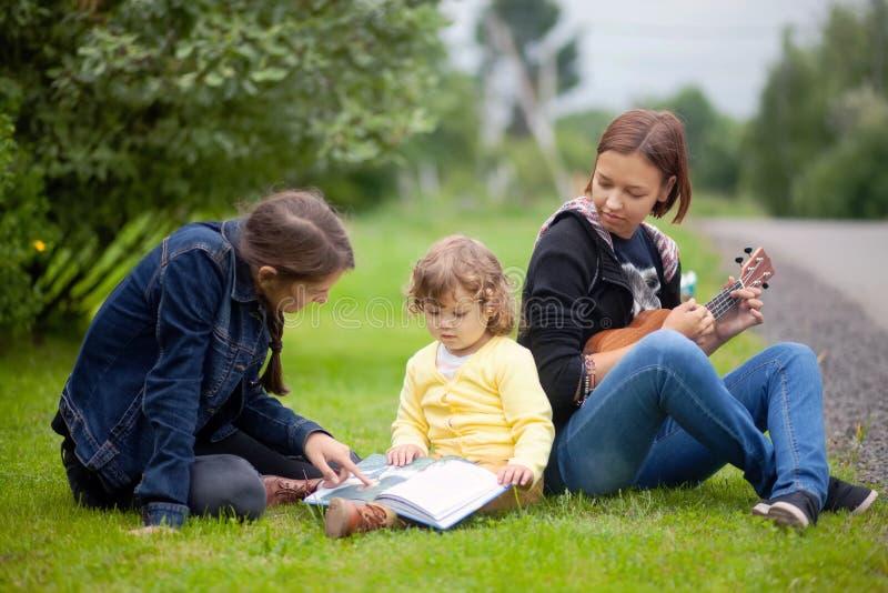 Kleines Mädchen, das Lesen lernt und Musikinstrumente, frühe vielseitige Entwicklung spielt stockbilder