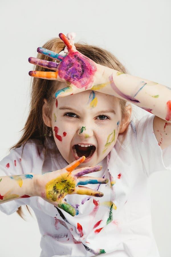 Kleines Mädchen, das lustige Gesichter bildet lizenzfreie stockbilder