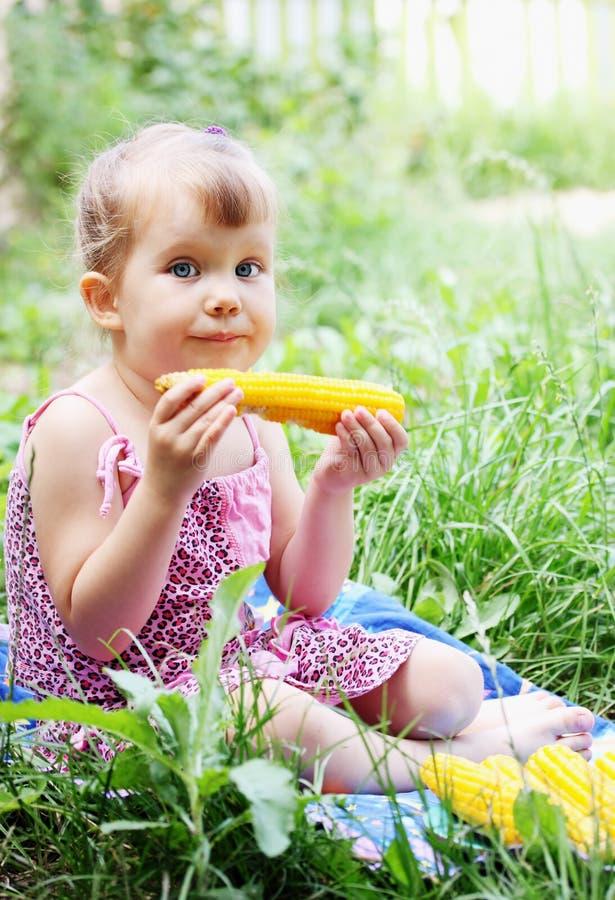 Kleines Mädchen, das Mais isst stockfotografie