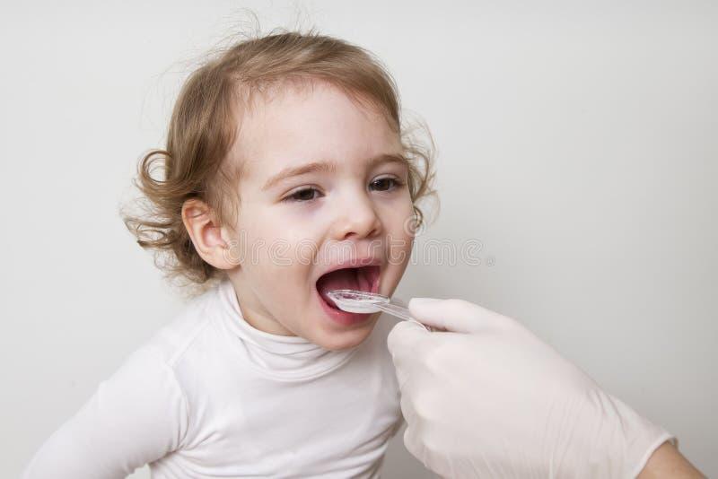 Kleines Mädchen, das Medizin mit Löffel einnimmt lizenzfreies stockfoto