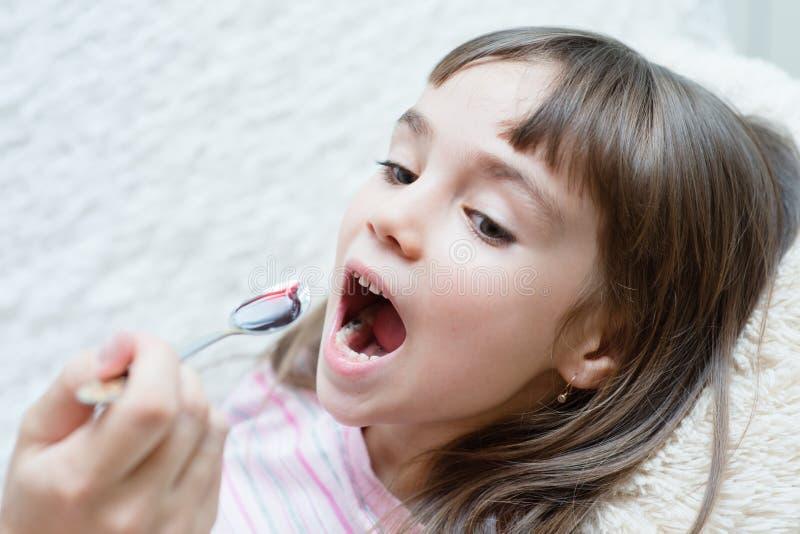 Kleines Mädchen, das Medizin mit Löffel einnimmt lizenzfreie stockbilder