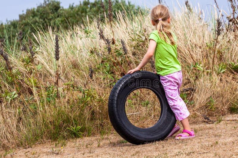 Kleines Mädchen, das mit altem benutztem faulem Abfallreifen auf trockenem Sommergras spielt lizenzfreie stockbilder