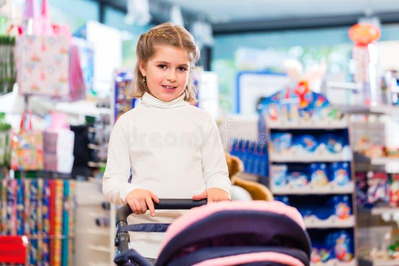 Kleines Mädchen, das mit Baby - Puppenwagen im Spielzeugsladen spielt stockfotografie