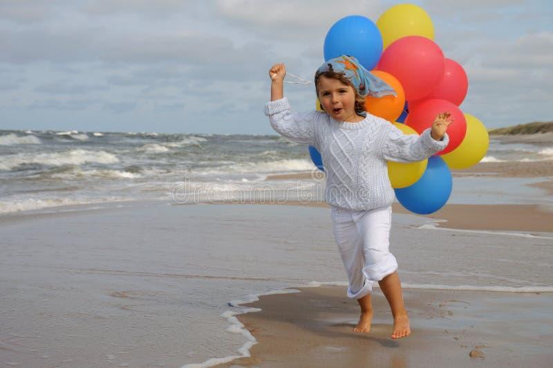 Kleines Mädchen, das mit Ballonen auf dem Strand spielt stockfotografie