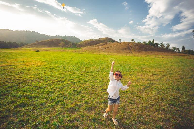 Kleines Mädchen, das mit dem Drachen glücklich läuft und auf Sommerfeld lächelt lizenzfreie stockbilder