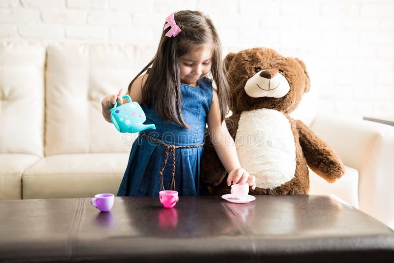 Kleines Mädchen, das mit einem Teesatz spielt stockfoto