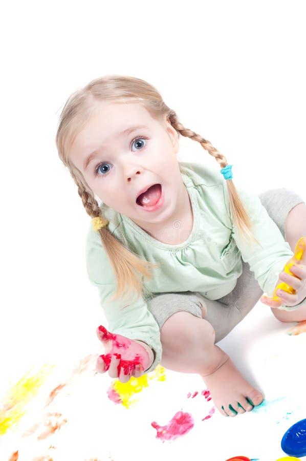 Kleines Mädchen, das mit Farben spielt stockfotos