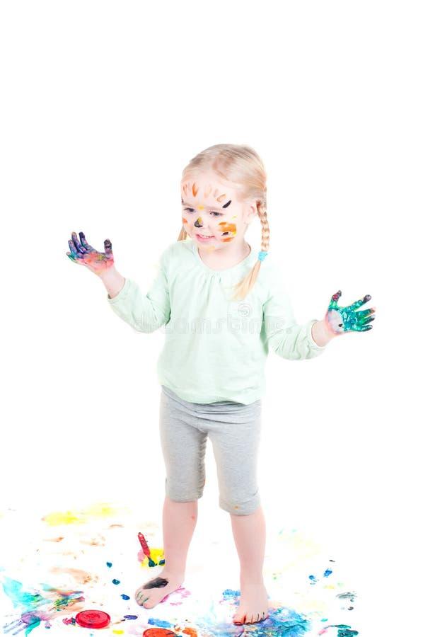 Kleines Mädchen, das mit Farben spielt stockbild