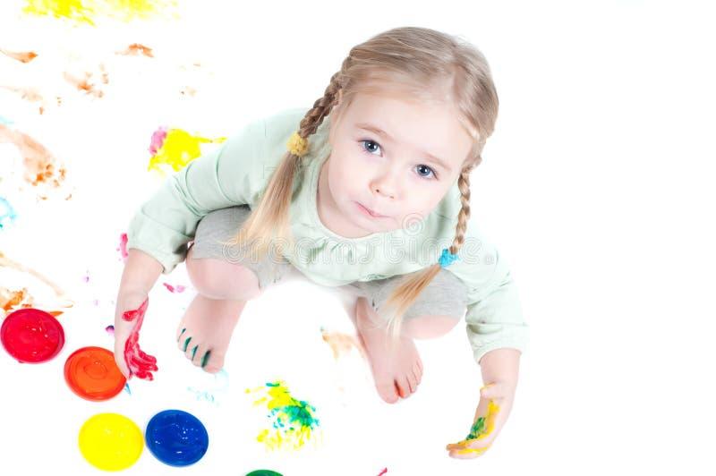 Kleines Mädchen, das mit Farben spielt lizenzfreies stockbild