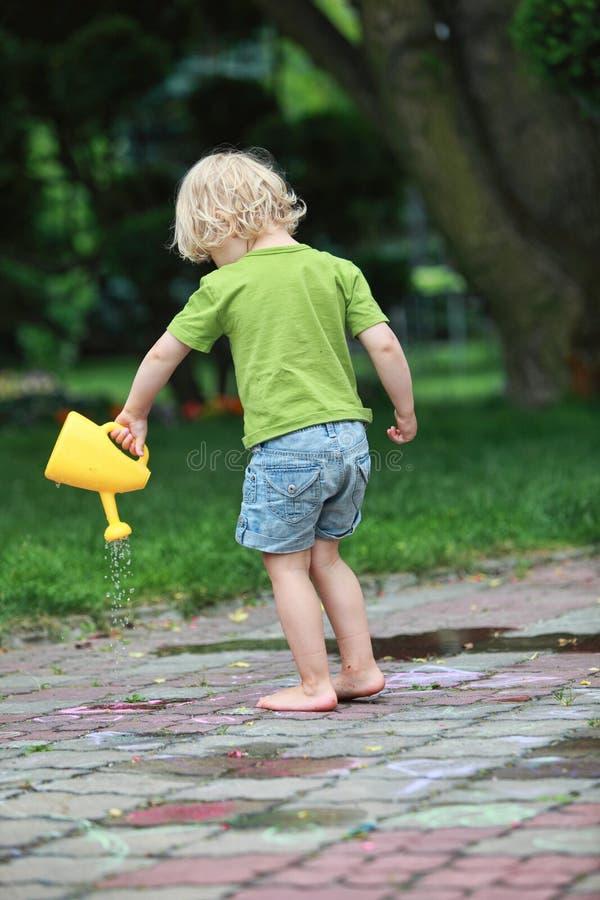 Kleines Mädchen, das mit Gießkanne spielt stockfotos