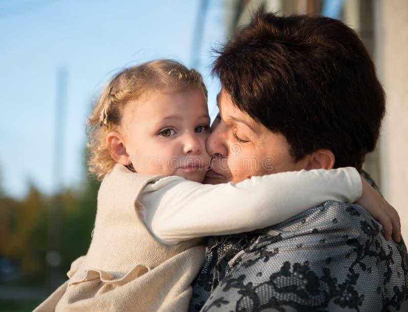 Kleines Mädchen, das mit Großmutter umfasst stockfotografie