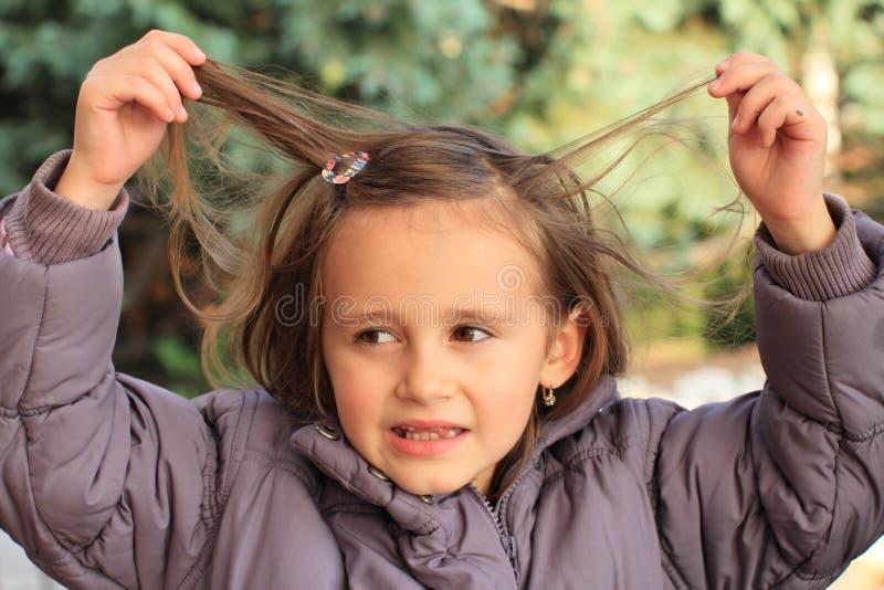 Kleines Mädchen, das mit ihrem Haar spielt lizenzfreies stockbild