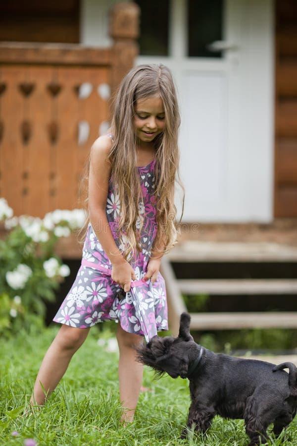 Kleines Mädchen, das mit ihrem Hund spielt lizenzfreie stockbilder