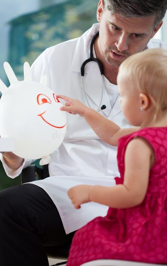 Kleines Mädchen, das mit ihrem Kinderarzt spielt stockfotografie