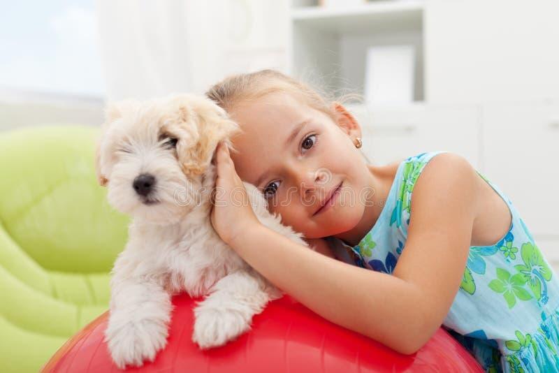 Kleines Mädchen, das mit ihrem kleinen flaumigen Hund spielt stockfotos