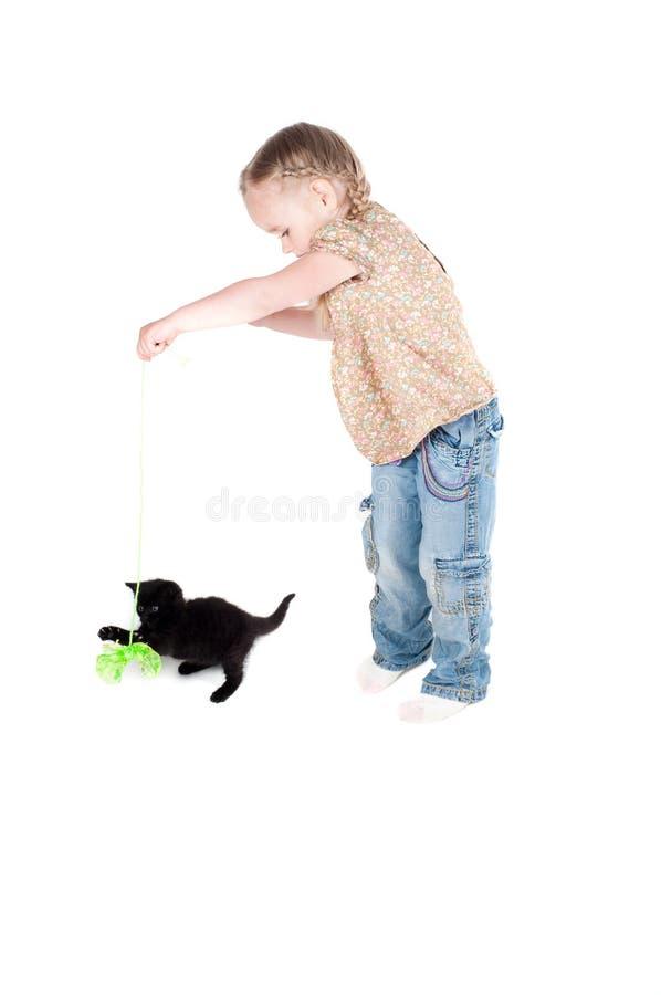Kleines Mädchen, das mit Kätzchen spielt stockfotografie