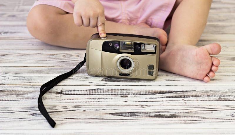 Kleines Mädchen, das mit Kamera, Nahaufnahmefoto spielt stockbild