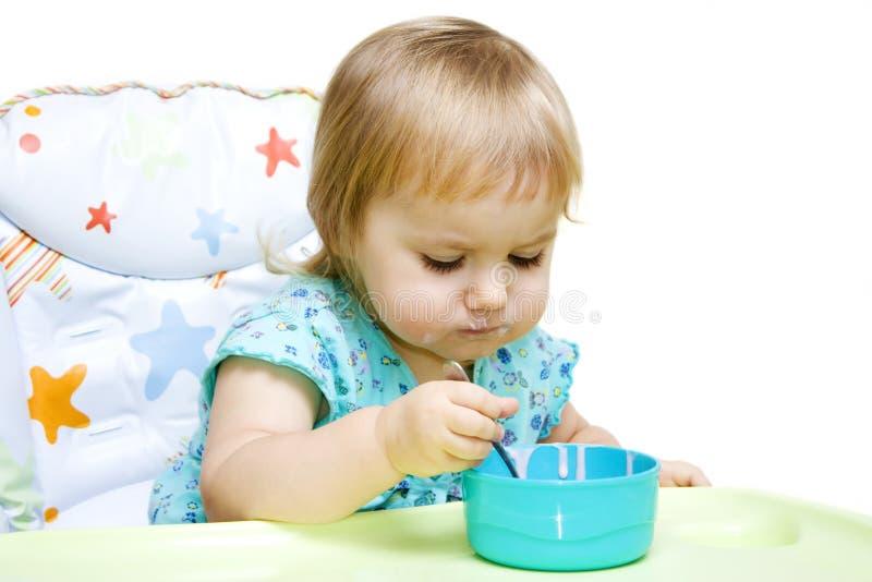 Kleines Mädchen, das mit Löffel isst stockfotos