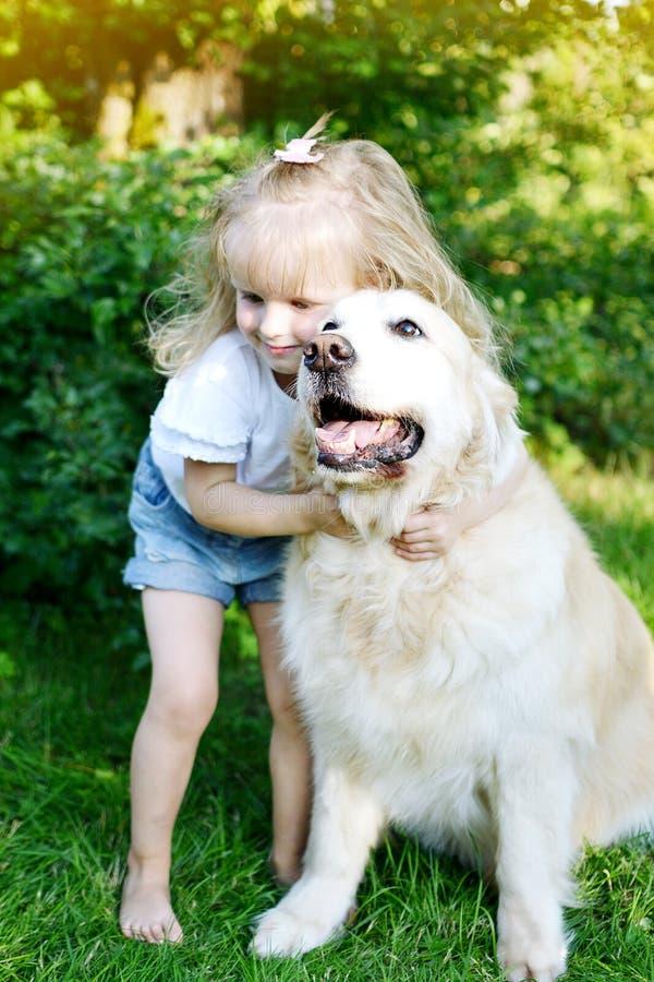 Kleines Mädchen, das mit Labrador-golden retriever im Sommerpark, grünes Gras spielt lizenzfreie stockfotografie